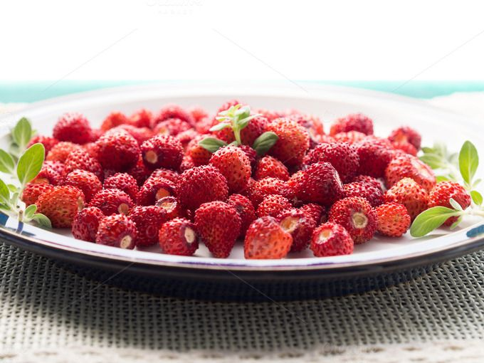 Wild strawberries on green table by Life Morning Photography on @creativemarket