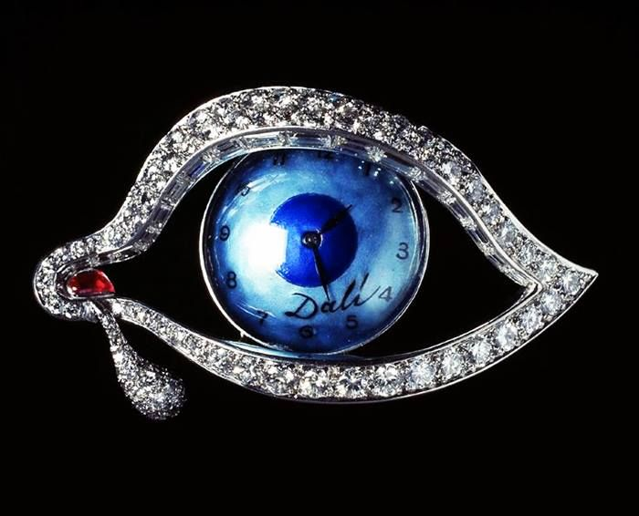 Brooch by Salvador Dali --The Eye of Time, 1949. Blue enamel, diamonds, platinum and cabochon ruby. The eye opens to reveal a blue-faced watch.