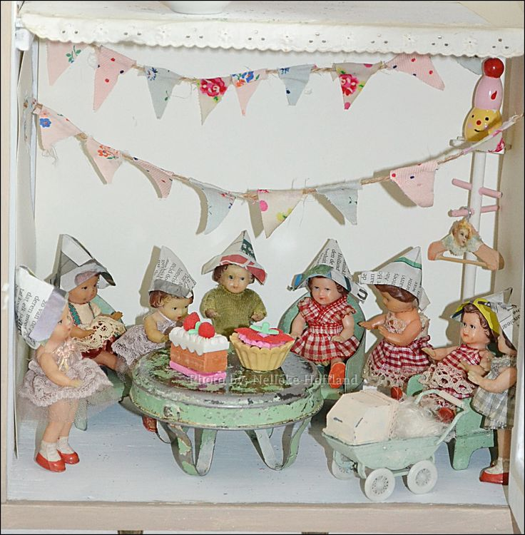 What a lovely way to display these petite dollies, love the wee pram an table
