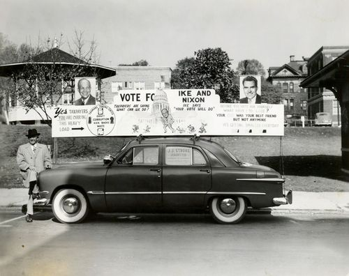 """Campaign car 1952 - Photo of an """"Ike and Nixon"""" banner mounted on top of an automobile, October 1952"""