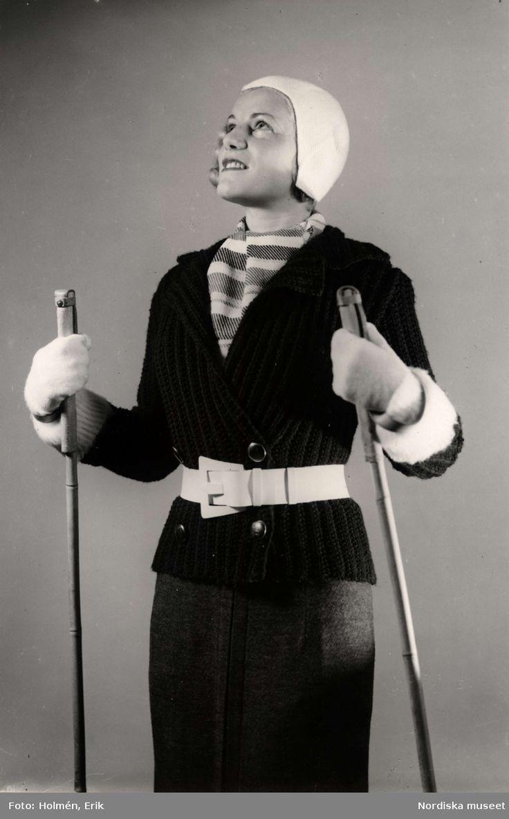 """""""Stickat"""", kvinnlig modell med en stickad kofta, vantar, mössa och halsduk. Hon håller ett par skidstavar i händerna. Varuhuset Nordiska Kompaniet i Stockholm visar vintermode 1936. Fotograf: Erik Holmén."""