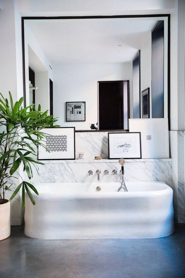 Bathroom with simple polished concrete floors, a floating tub, and a large mirror