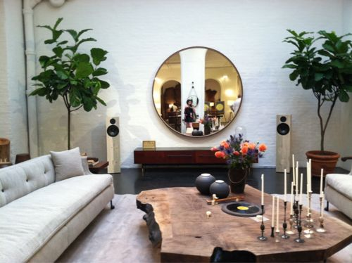 Contemporary round mirror to modernize dark wood furniture. Greenery for warmth and classing.