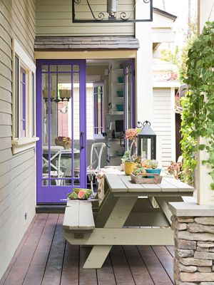 Patio Dining. The home's blue French doors provide plenty of bright color for this patio. Because the patio is adjacent to the home's kitchen, the simple picnic table is great for taking meals outside.