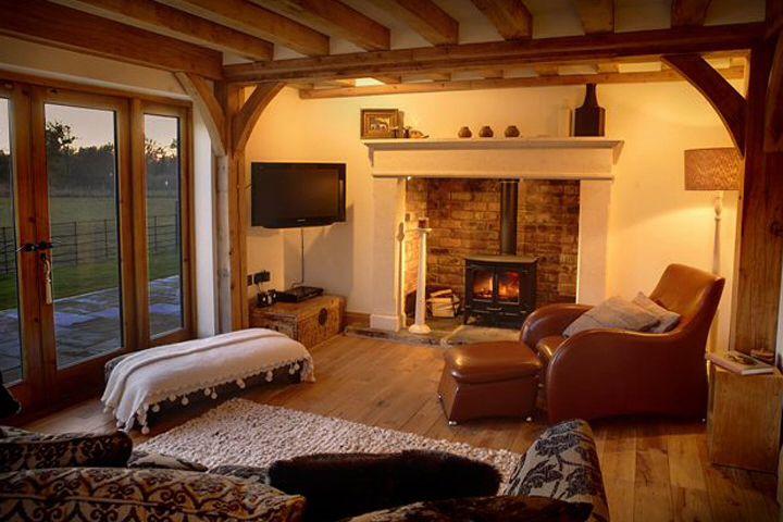 Cosy lounge exposed oak beams, large glazed French  doors, exposed brickwork, wood burning stove, leather armchair,