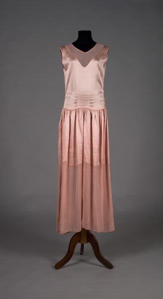 MMT 001114 :: klänning, aftonklänning c. 1925 Aftonklänning av rosa satin, ärmlös med rundad urringning, i ryggen med V-formad isättning av georgette med 2 löst hängande sleifar, horisontalla stråveck; kjolen vid och rynkad, övre delen av satin som nedtill avslutas med mjuka rundlar och sammansydd med en nedre del av georgette, blomma i färg på höften, sprund med tryckknappar i vänster sida.