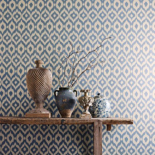 Surin Wallpaper A bold wallpaper with a medium scale non-uniform ogee pattern shown in shades of beige. The design has been printed to resemble hand-crafted fabric and is inspired by a divine silk warp printed ikat from the Sanderson archive.