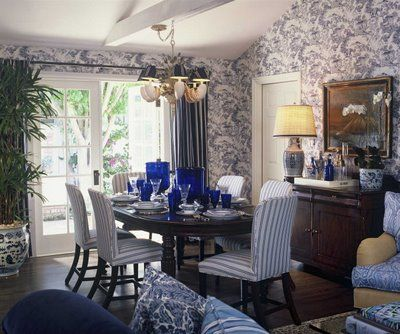 traditional dining room with blue tolie wallpaper, upholstered