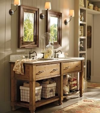 A place for everything, and a few well-placed details, help this bathroom feel structured but not austere. Natural materials – the wood of the console, the marble sinks and countertops, and the rustic hardware – give this room an especially beautiful and soothing appearance. Lined baskets provide roomy, concealed storage. A plush rug in autumnal colors adds rich color and definition
