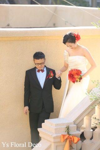 こちらのおふたりのお色直しのときのご様子です。ドレスはそのままに、お花でイメージチェンジです。太陽を感じさせる赤やオレンジの色合いで、クラッチブーケをお作...