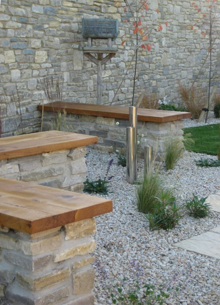 Stone walls capped with timber slabs for seating.
