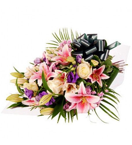 Beautiful pink lilies and chrysanthemums complemented with white roses and with blue lisianthus make this a delicate floral tribute.