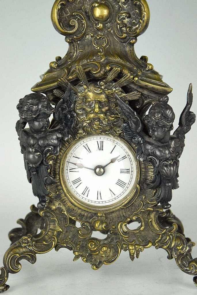 (B) Obelisk form clock with thermometer. Metal base with foliate and angel decoration. Black marble obelisk stem surmounted by an angel with horn having a floral finial...