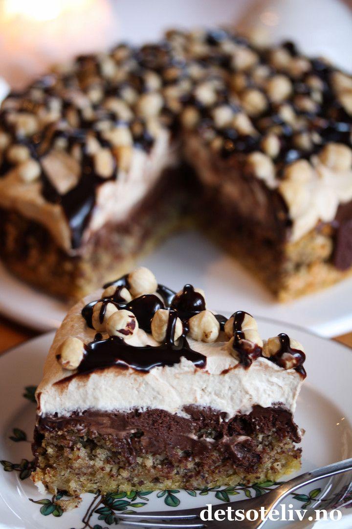 """Her er et herlig kaketips til helgen! """"Nøttekake med sjokolade og kaffekrem"""" er den mest leste oppskriften på NRK Mat i 2014! Jeg måtte såklart også teste kaken, og den var veldig, veldig god.  Kaken består av en meget myk nøttebunn som synker sammen i midten etter at den er ferdigstekt. Det passer bra, for gropen fylles med et deilig sjokoladefyll. På toppen dekkes kaken med luftig kaffekrem, som smaker deilig til resten. Jeg har pyntet kaken med hele hasselnøtter og sjokoladesau..."""