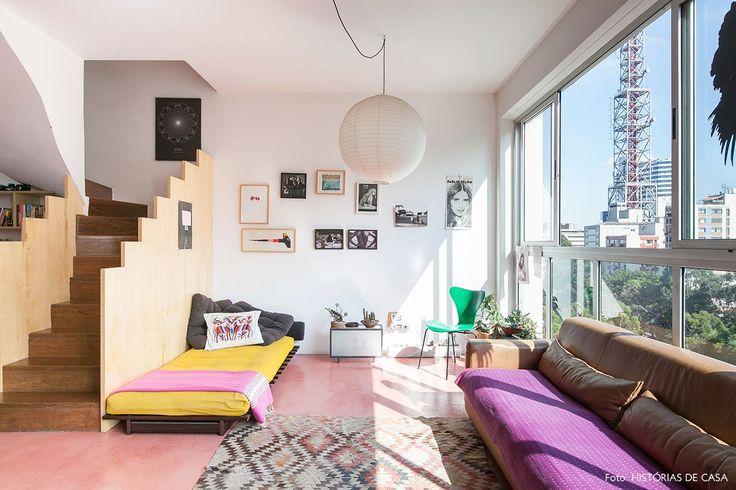 Sala de estar em apê duplex na Av. Paulista tem piso de cimento queimado rosa, parede galeria e sofá de couro.