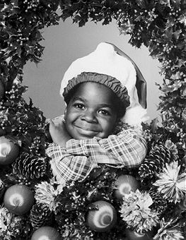 American child actor Gary Coleman wears a Santa Claus hat and peers through a holly wreath decorated with Christmas ornaments and pine cones in a promotional headshot portrait for the television series 'Diff'rent Strokes'.