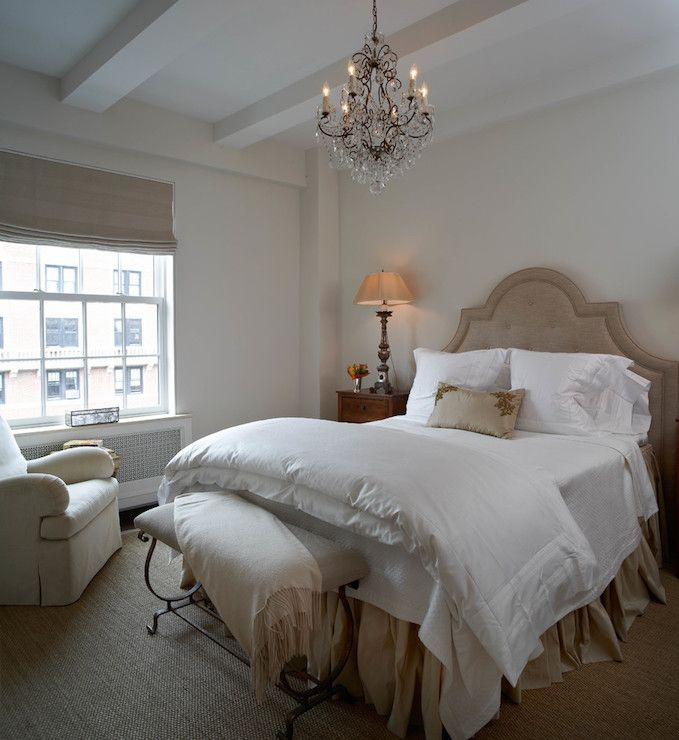 Elegant bedroom features a beige tufted headboard on full bed dressed with white bedding with stain trim and gold pleated bedskirt flanked by wood nightstands topped with tall lamps alongside a wrought iron bench placed at the foot of the bed illuminated by a crystal chandelier.