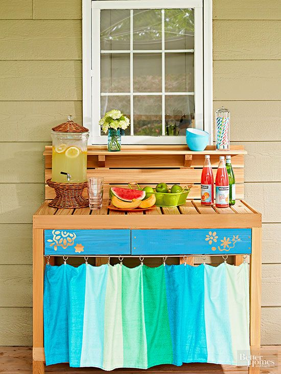 Practicality is key to increasing the use of any patio space. Storage and organization locations, such as this DIY patio beverage station, offer spots for gathering. Customized from an off-the-shelf workbench, special touches to this project include paint on the drawer fronts and an easy-sew curtain to hide supplies./
