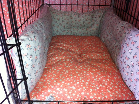 our dog loves to have pillows and blankets around the edge of his crate. i like this idea. we'll try it with cheap body pillows and some diy straps to secure them to the frame of the crate...probably with a more durable cover on all the pillows that will hold up to a 60lb husky mix rooting around in his bed. lol!