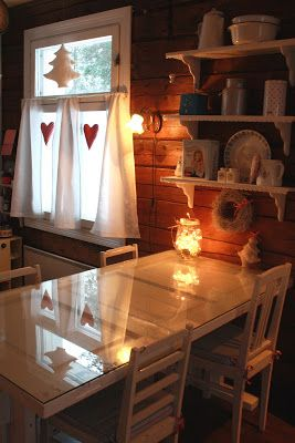 Tiny kitchen table, made from an old door, with DIY legs. A jar of fairy lights adorns the table, under the open shelving. Site in Finnish. | Tiny Homes
