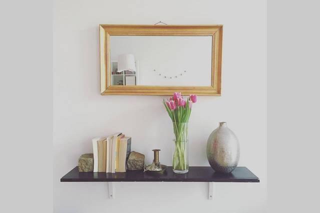 Schlichte, stilvolle Deko-Idee: Spiegel mit Goldrahmen, Vase, Blumen und Bücher auf Wandregal - Schönes Zimmer in 3er-WG - Wohngemeinschaft Berlin-Wedding #Spiegel #Goldrahmen #BerlinWedding