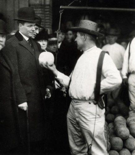Kaasmarkt Alkmaar. Kaasdrager biedt Amerikaanse gezant Philips (met bolhoed) en achter hem M.C. Wendelaar, burgemeester van Alkmaar, een Edammer kaas aan. Nederland,