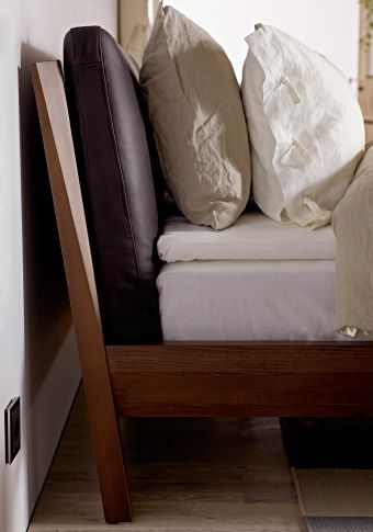 Close-up of IKEA wooden bed with leather cushions and bedding.