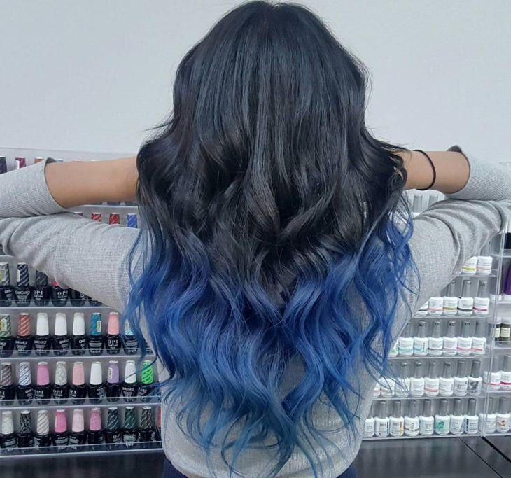 mujer de espaldas con cabello negro y puntas de colores azules