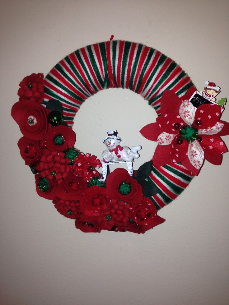 Christmas wreath. Base made out of yarn. Hand-made felt flowers. Added snowman on sledge, wooden sign.  More at https://www.facebook.com/Moje-vence-995508700482994/