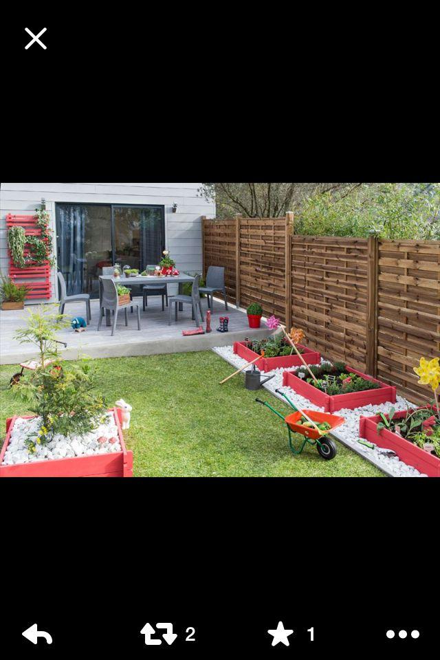 Palissade bois + terrasse grise + bardage + petits pots rouges dans cailloux gris