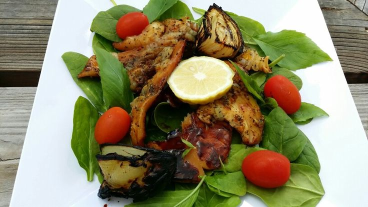 Roast conch on baby spinach with cherry tomatoes.