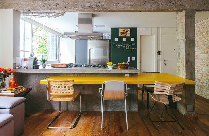 Cozinha integrada à sala com bancada  de concreto e mesa revestida de fórmica amarela.