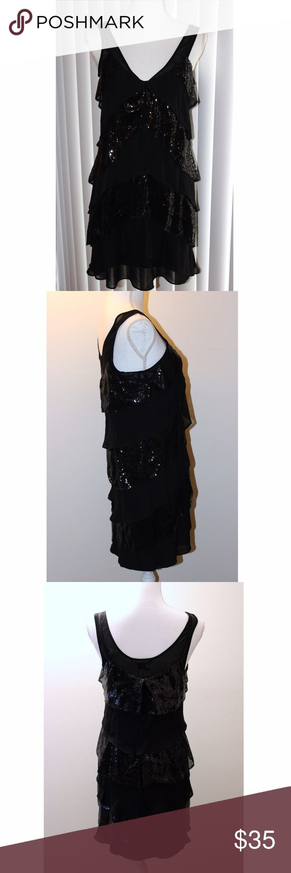 "Armani Exchange Black Sequined Dress Make a statement in this little black sequined dress! It has a sheer lining covered by layers of small sequins and ruffles. The lining is connected to the dress on the shoulders. The lining is stretchy - the rest is not. It is made of polyester and satin. Measurements: Armpit to armpit 15.5""; Waist 36""; Hips 39""; Length 31"". The dress is new with tags by Armani Exchange and is a size 6. Armani Exchange Dresses Mini"