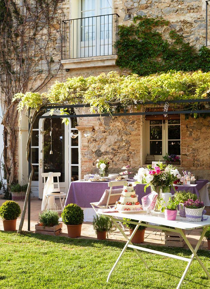 Comedor bajo techo de parra y mesa auxiliar con tarta y flores en tonos lilas 00343923 O