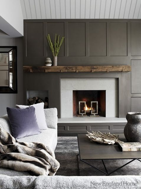 a modern paneled fireplace in a soothing grey color palette adds to the appeal of this living room featured in new england home