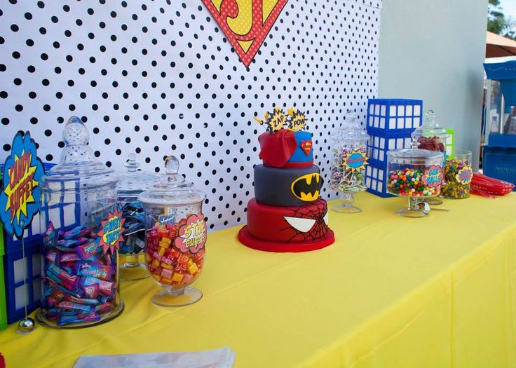 """The candy buffet and cake table was one of the highlights of the party! The background featured black polka dots, which reminded guests of the older comic book days. It also featured the Superman symbol with a """"J"""" for the birthday boy, James!"""