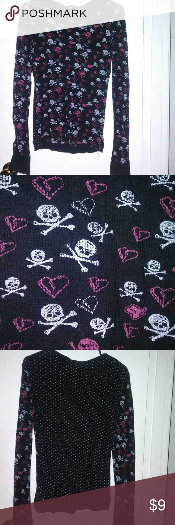 Long Sleeved Skull & Bones Shirt A black long sleeved shirt with pink and white skull & crossbones, broken hearts, and Fox brand logos. The front and sleeves have that pattern, but the back has pink and white polka dots. There are 4 buttons by the neck of the shirt that are functioning. Has been loved, but is in great condition. Fox Tops Tees - Long Sleeve