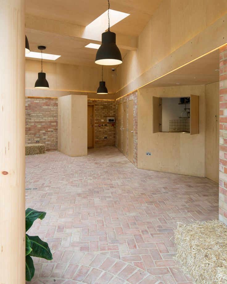 The brick flooring extends from the courtyard and garden pathways into the multipurpose hall, where the bricks are laid in decorative patterns.