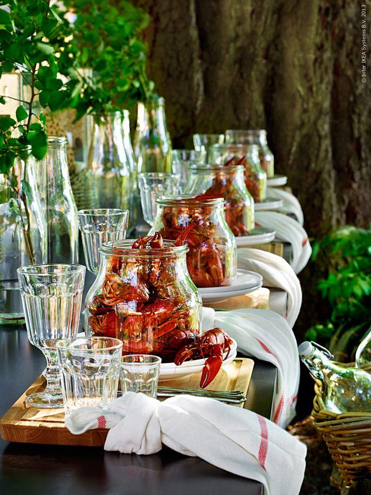 Årets kräftskiva dukar vi upp under trädkronorna. Längs långbord sittandes på bänkar blir gästerna serverade kräftor i varsin egen glasburk. Några plädar, brödkorgar, sånghäften och väl tilltagna servetter gör  kalaset komplett. Och ovanför huvudet svävar kräftorna på rad i en  enkelt fixad dekoration av rep och skrynklade papper. Anna & Pernilla, för Livet Hemma
