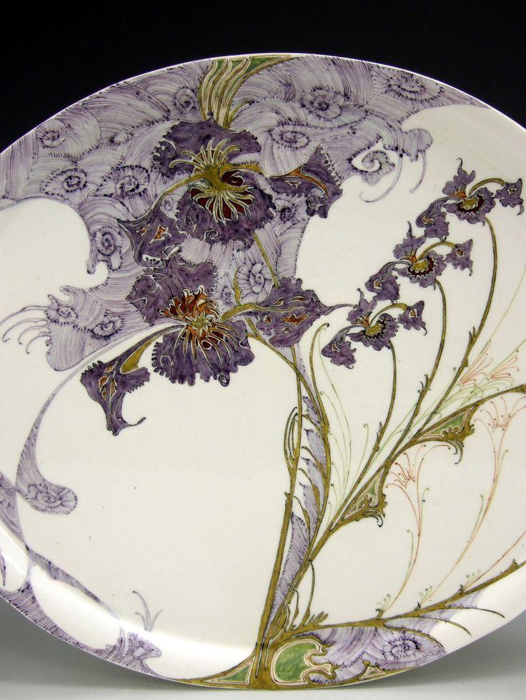 Een zeldzaam Rozenburg ovaalvormig theeblad van eierschaal porselein, beschilderd met paarse orchideeën. Het blad is 26,5 cm bij 30,7 cm groot, model 63. Gemerkt met het fabrieksstempel, het monogram van de schilder Sam Schellink en de jaarcode 1900, werkordernummer 594.    Van dit blad, model 63, zijn slechts 16 stuks in totaal gemaakt door Rozenburg en dit