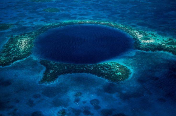 """Blue Hole"""" (foto), no centro do atol Lighthouse Reef, a verdadeira obra-prima de Belize. Trata-se de uma circunferência escavada pela natureza no meio da barreira de corais, com mais de 300 metros de diâmetro e 135 metros de profundidade, onde mergulhadores experientes encontram enormes estalactites e estalagmites, algumas com mais de cinco metros de comprimento."""
