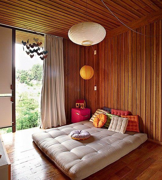 Para o pequeno Raul, 2 anos, nada de berço. O menino dorme em um futon cheio de almofadas no quarto de madeira. Para completar a decoração descolada, luminárias de papel de arroz e um móbile de pássaros. O criado-mudo é um cubo de espuma. Projeto da arqui