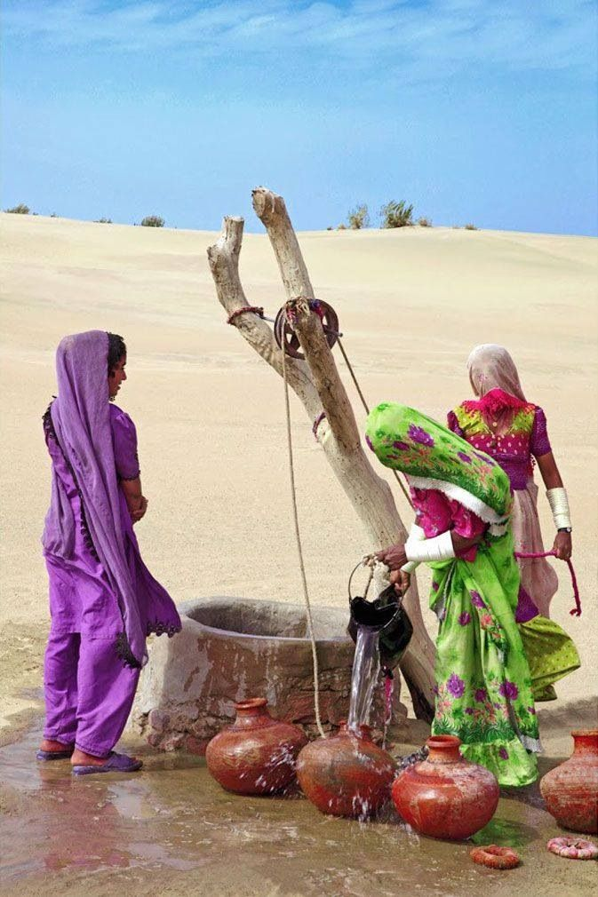 Indian village women getting their day's water supply.