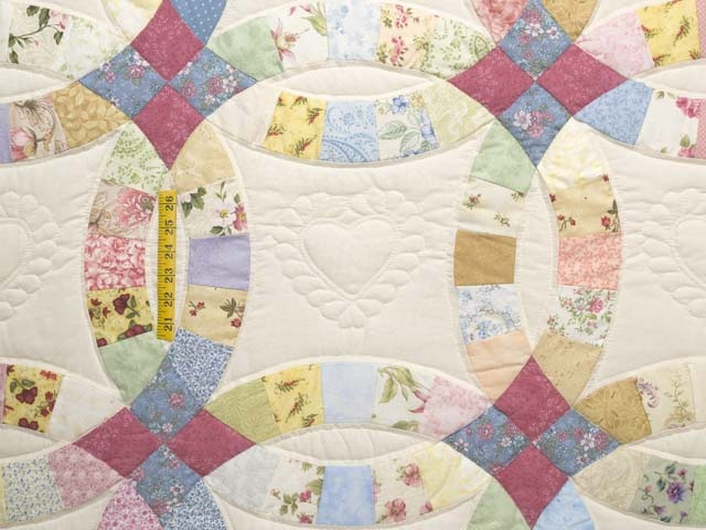 pastel double wedding ring quilt medallion in the center echo quilted the pieced arcs - Wedding Ring Quilt