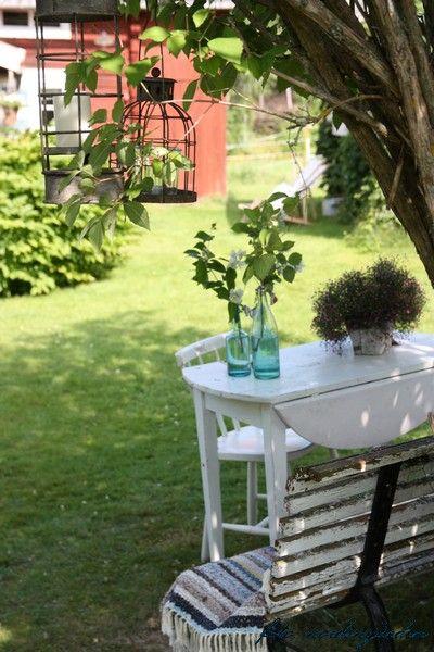 via nordingården. Lanterns hang on the tree. Small garden oasis easily doable.