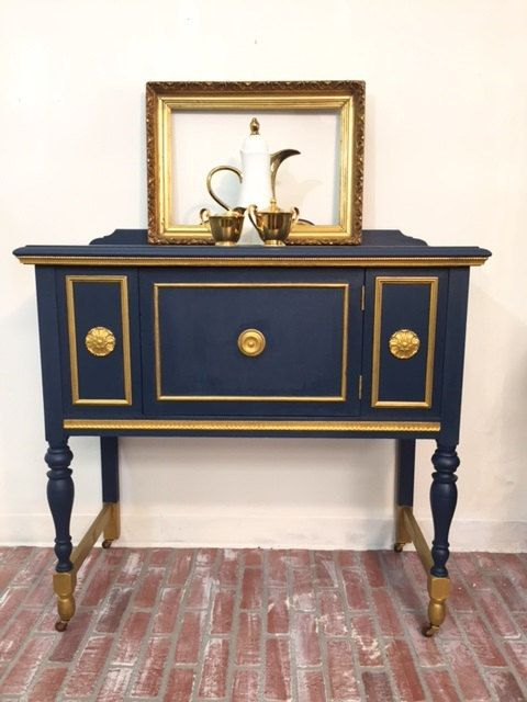 SMALL VINTAGE BUFFET TABLE  You will make a statement with this beautifully hand-painted 1940s side server. This elegant lady could be used in an entry hall , dining room or even as a wine cabinet. She is painted a deep navy blue with gold accents, and is in very good vintage condition.  It measures 38 inches wide x 18 inches deep x 35 inches high.  * * * PLEASE READ SHIPPING & POLICIES PRIOR TO PLACING AN ORDER * * *  THE SHIPPING AMOUNT SHOWN IS FOR THE EASTERN UNITED STATES ONLY! If you…