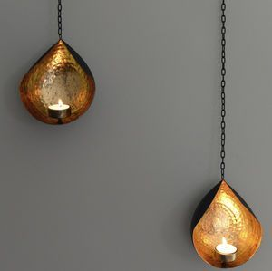 Hanging Gold And Black Tea Light Holder   Bring summer evenings in with this luxurious trend. Think dark, elegant colours alongside warm lighting and reflective surfaces. Achieve this look by combining dark velvets with high-gloss furniture and multiple light sources such as fairy lights, lanterns and floor lamps.