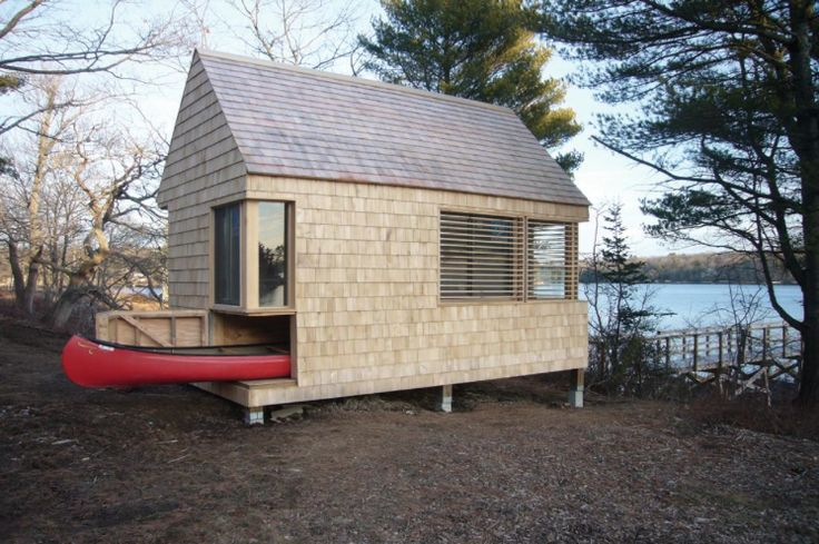 """combines two functions; writing studio and boat house. The small190 square foot """"block"""" was conceived by interlocking program and allowing design elements to double function. Canoe storage = combination workspace + bed. Interior structure = book + utility shelving. The windows and awning are arranged to maximize views and allow passive heating and cooling. These elements were""""carved"""" out from the traditional saltwater barn form, animating the exterior, but allowing a peaceful interior."""