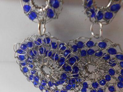 Orecchini  pendenti fatti  all'uncinetto con metallo colore argento e cristalli azzurri .
