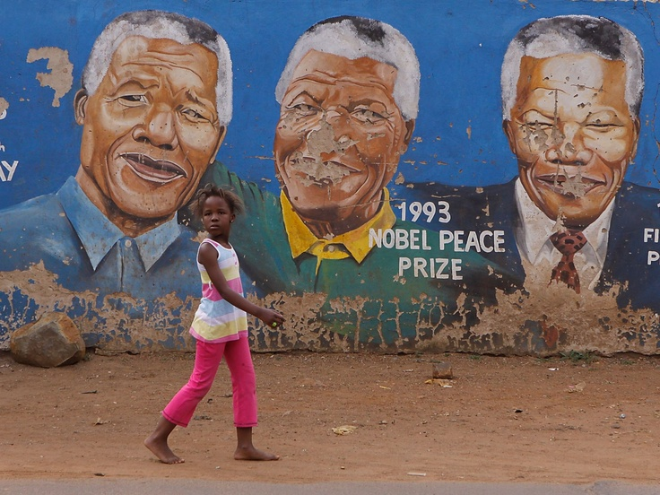 A child walks past portraits of former South African president Nelson Mandela on March 28 in Soweto. Mandela, the anti-apartheid leader who became South Africas first black president, has been hospitalized because of a lung infection.  Denis Farrell, AP